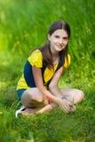 Une fille s'asseyant sur l'herbe verte Photographie stock libre de droits