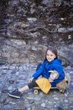 Une fille s'asseyant sur la planche à roulettes et tenant le bateau de jouet Photo libre de droits