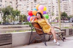 Une fille s'asseyent sur une banque avec des ballons photos libres de droits