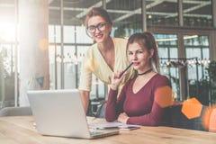 Une fille s'assied à la table devant l'ordinateur portable, en second lieu se tient à côté de elle Effet de film Filles blogging Photo stock