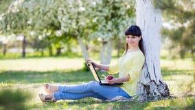 Une fille s'assied avec un ordinateur portable près d'un arbre images stock