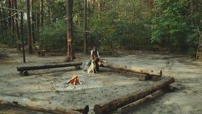 Une fille s'assied dans la forêt lisant un livre La fille s'assied sur un rondin à côté du feu et lit un livre banque de vidéos