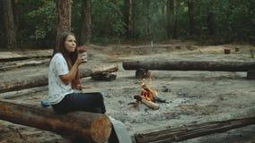 Une fille s'assied dans la forêt lisant un livre La fille s'assied sur un rondin à côté du feu et lit un livre, plan rapproché banque de vidéos