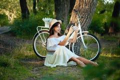 Une fille s'assied sur l'herbe et prend une photo au téléphone photo stock