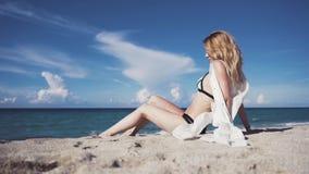 Une fille s'assied sur le sable et la prend un bain de soleil clips vidéos