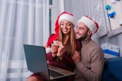 Une fille s'assied sur son recouvrement près du type avec un ordinateur portable faisant le pok Photos libres de droits