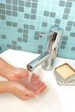 Une fille se lave les mains Photo stock