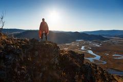 Une fille se tenant en collines au coucher du soleil images libres de droits