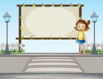 Une fille se tenant le long de la route Image stock