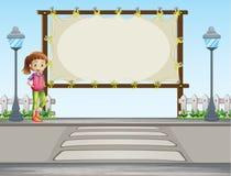 Une fille se tenant près d'un signage vide Image stock