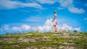 Une fille se tenant sur la colline et regardant les nuages blancs, collines de Teletubbies, Nusa Penida, Bali, Indonésie Images stock