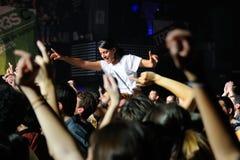 Une fille se tient au-dessus de la foule dans un concert à la discothèque de clinquant Image libre de droits