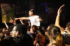 Une fille se tient au-dessus de la foule dans un concert à la discothèque de clinquant Photos stock