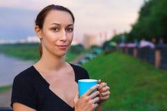 Une fille se tient avec la tasse de thé Photos libres de droits
