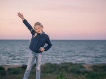 Une fille se tient dans l'herbe avec sa main augmentée sur la côte Images libres de droits