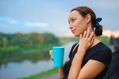 Une fille se tient dehors avec la tasse de thé Photographie stock libre de droits