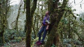 Une fille se tient se penchante contre un arbre couvert de mousse dans une forêt mystérieuse banque de vidéos
