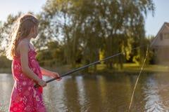 Une fille se tient prêt la canne à pêche par un lac image stock