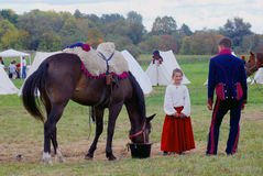 Une fille se tient prêt un cheval Image stock