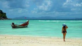 Une fille se tient sur la plage et regarde un bateau thaïlandais traditionnel de longtail banque de vidéos