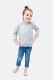 Une fille se tient sur le fond gris Images stock