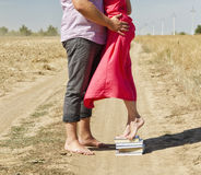 Une fille se tient sur une pile de livres pour atteindre et embrasser le type Photographie stock