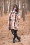 Une fille seule couverte de couverture et de café de boissons d'une tasse thermo dans la forêt images stock