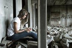 Une fille seule dans un T-shirt blanc et des jeans s'assied sur les ruines d'une maison ruinée Expression triste, l'atmosphère tr Images libres de droits