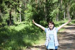 Une fille soulève ses mains au ciel dans une forêt ensoleillée d'été Photographie stock
