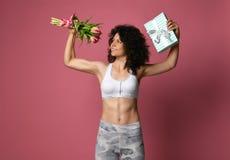 Une fille sportive de beau corps avec les cheveux bouclés et dans les vêtements de sport, tient dans un bras musculaire fort un b images stock