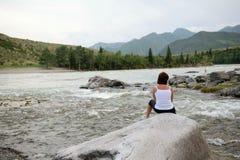 Une fille sur la berge s'assied sur une roche Photo stock