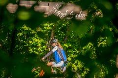 Une fille sur la bicyclette vue par des arbres photos libres de droits