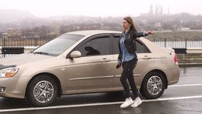 Une fille sur une route pluvieuse vide demande l'aide et les arr?ts passant des voitures clips vidéos