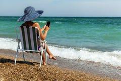 Une fille sur une plage travaille à un téléphone photos stock