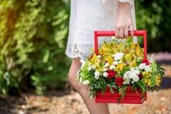 Une fille tenant une belle composition des fleurs dans des ses mains photos stock