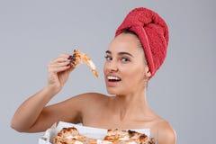 Une fille tenant une bouchée du morceau de pizza appétissant sur un fond gris photo stock