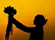 Une fille tenant des fleurs de lotus au coucher du soleil Photos libres de droits