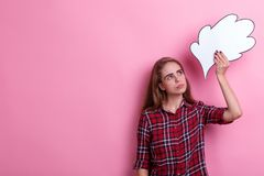 Une fille tenant une image de papier d'une pensée ou d'une idée aérienne la regardant et recherchant Sur un fond rose Images libres de droits