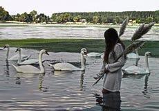 Une fille tenant le jonc et appelle les cygnes blancs Photo libre de droits