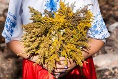 Une fille tenant un bouquet des wildflowers frais Femme dans le costume national ukrainien avec un bouquet image stock