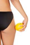 Une fille tenant une orange à côté des fesses Photo stock