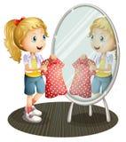 Une fille tenant une robe rouge devant le miroir Image libre de droits