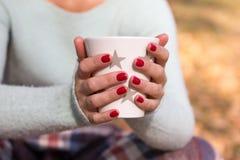 Une fille tenant une tasse avec une boisson Images libres de droits