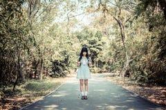 Une fille thaïlandaise asiatique mignonne se tient sur seul un chemin forestier dans le vin Image stock