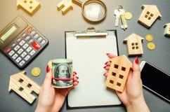 Une fille tient dans des ses mains des dollars et une maison miniature Le concept de l'évaluation des risques pour l'achat des im photo libre de droits