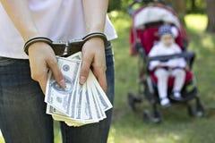 Une fille tient des dollars d'argent dans des menottes contre le contexte d'un bébé dans un chariot, arrestation, trafiquant chez photo libre de droits