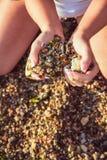 Une fille tient des pierres dans des mains dans une forme d'un coeur photographie stock libre de droits