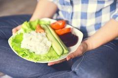 Une fille tient un plat avec du riz et des légumes photographie stock libre de droits