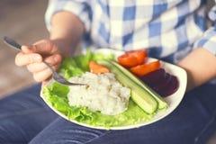 Une fille tient un plat avec du riz et des légumes photographie stock