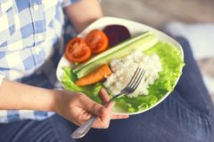 Une fille tient un plat avec du riz et des légumes image libre de droits